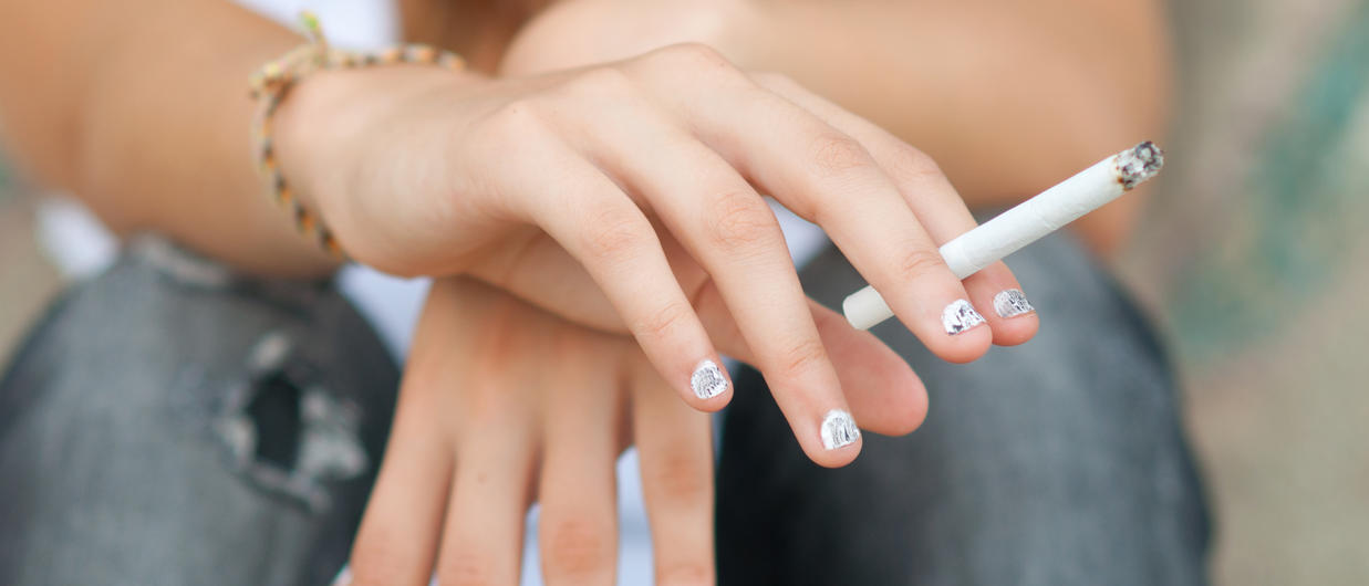Teen hands holding cigarette