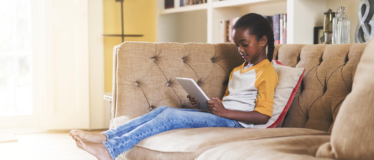 Little girl sitting on couch reading alone