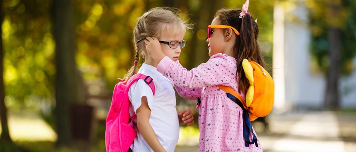 Little girl helping another girl with her glasses