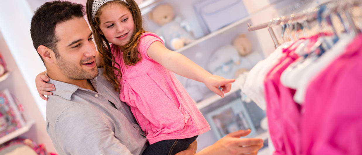 Father letting little girl pick out a dress