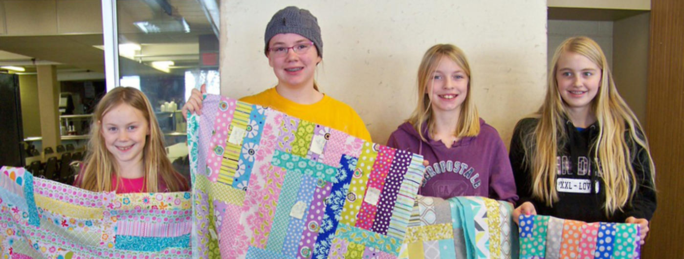 four girls holding quilts