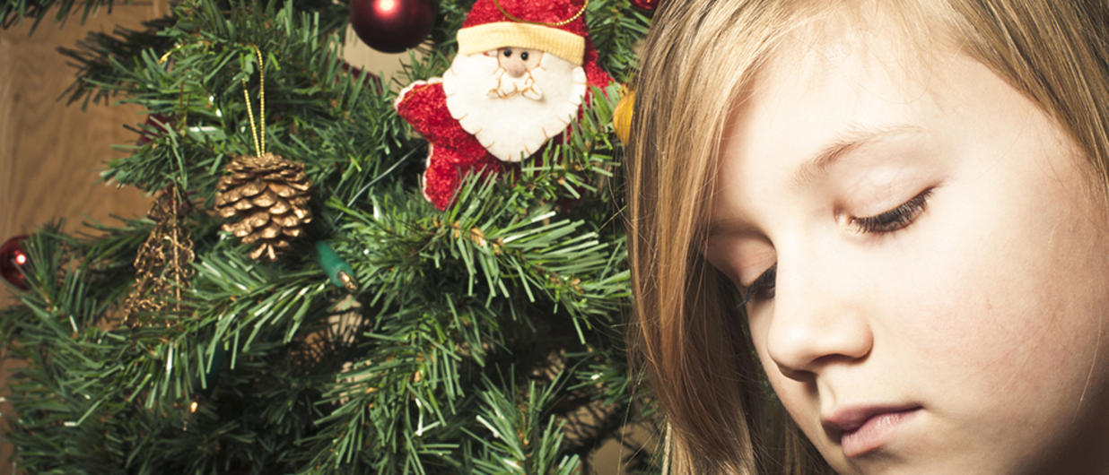 Child looking sad in front of Christmas tree