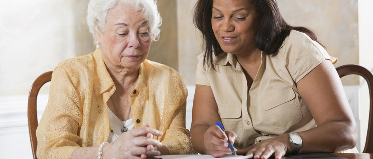 Woman showing elderly woman some paperwork