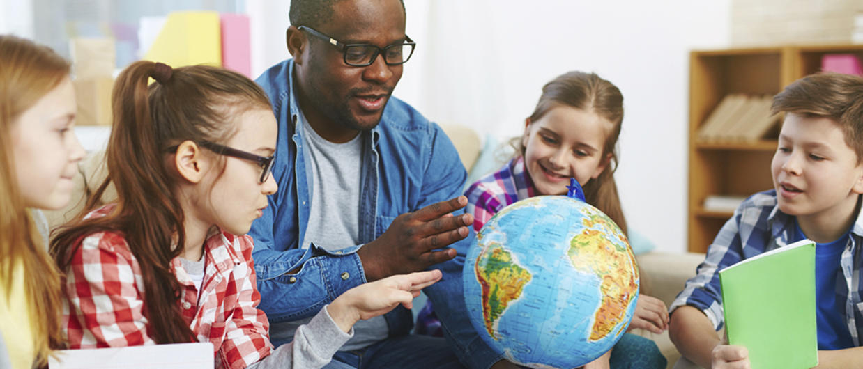 Teacher showing globe to students