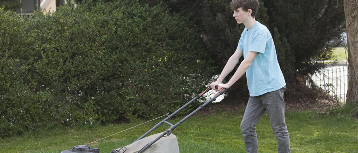 Boy pushing lawn mower