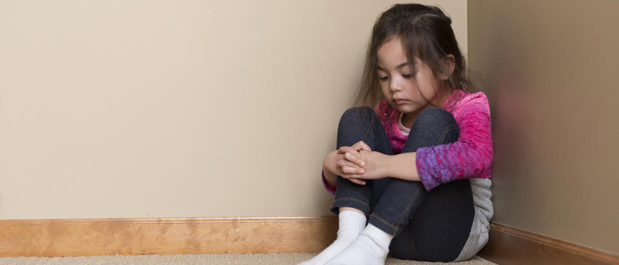 Little girl sitting in corner