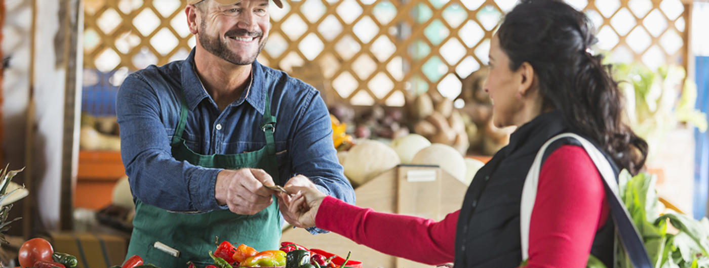 Woman paying farmer at farmers market