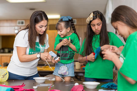 Three elementary age girls participate in STEM activities with 4-H leader.