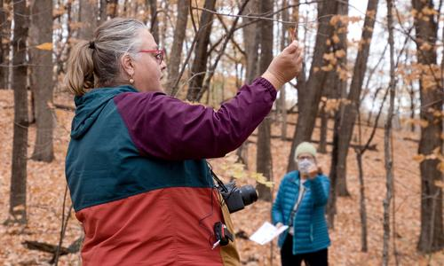 Amy Rager teaching about trees in a fall woods.