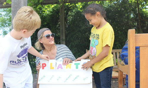 adult volunteer with a poster board that says PLANTS and each letter stands for something plants need, such as light and nutrients