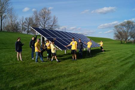 Group of people around a ground mounted solar panel.