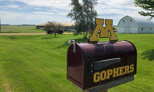 U of M Gophers mailbox in front of farm fields and white farm building