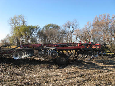a disk ripper plow which has three rows of disks facing opposite directions and two rows of tines in between the disks.
