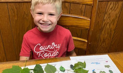 Boy wearing red shirt that says Country Roads on it sits in front of his nature bingo card with leaves he has collected