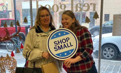 "Two women holding ""Shop Small"" sign inside retail store."