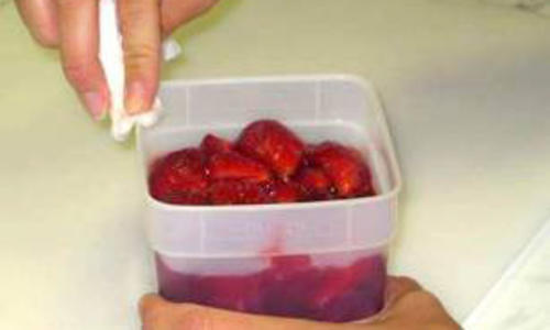 Wiping rim of berry container.