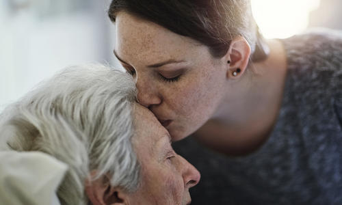 woman kissing senior woman on forehead