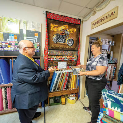 CJ Holl visiting in Kristi Feist in her Wells, Minn. quilt shop. Quilts and fabrics are on the wall behind them.