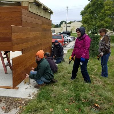 Volunteers help to build a wooden bike shed