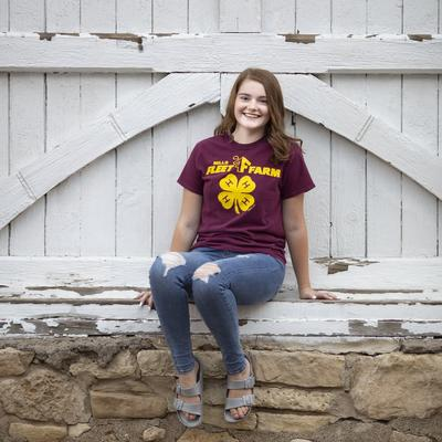 Abbey Rademacher sits on a distressed rock wall smiling, she wears a maroon and gold 4-H t-shirt.