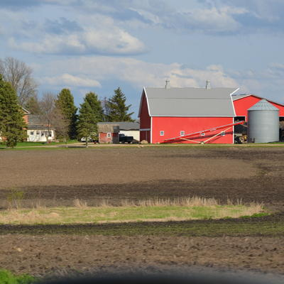 Farm field with red barn and silos in the distance.