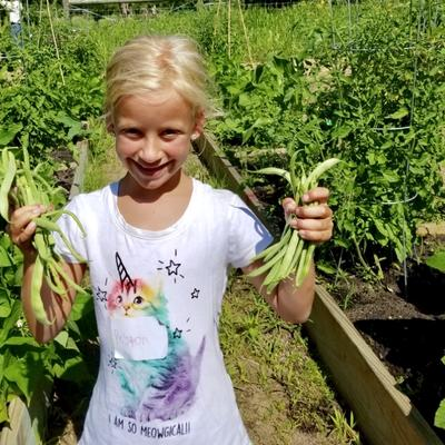 girl holding up beans she picked and smiling in the garden