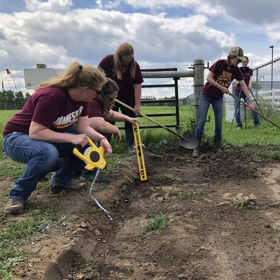 several students help measure and prepare a horse pasture traffic pad