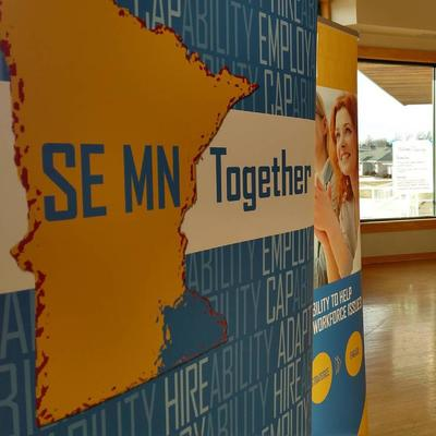 SE MN Together banner on the left, people sitting around a table having discussion.