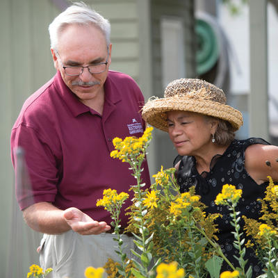 Man and woman examining flowers in garden