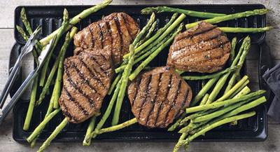 four steaks surrounded by asparagus on a grill