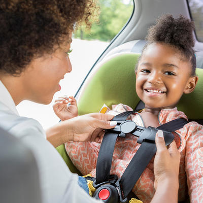 Child being buckled into car seat