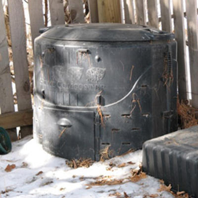Compost bin by a wooden fence in a yard during winter with snow