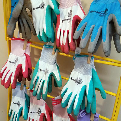 Rack of colored gardening gloves hanging to dry.