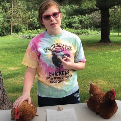 4-H'er giving a talk about chickens outside