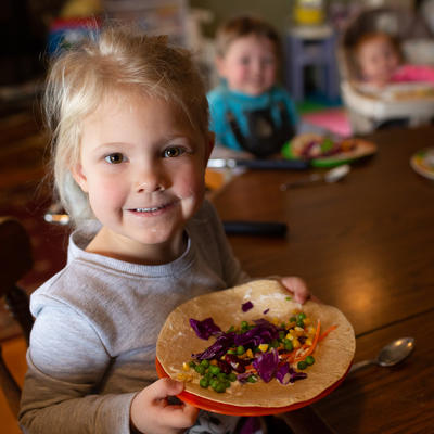 Girl with veggie wrap at kitchen table