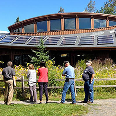 Group of adults looking at the Hartley Nature Center building with solar panels on roof. Source: Alison Hoxie.