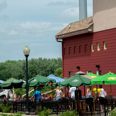 People gathered outdoors on a patio with umbrellas at a brewery.