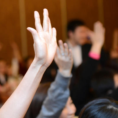Raised hands in a meeting