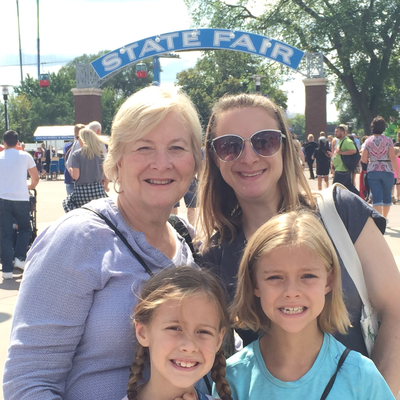 Martha Metz and her daughter and two granddaughters in front of Minnesota State Fair arch