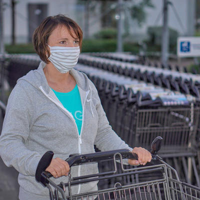 Person holding a shopping cart wearing a mask