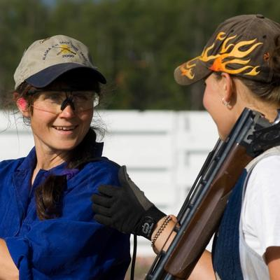 girl with rifle talking to instructor