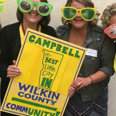 Four ladies wearing fun-oversized glasses holding a sign reading 'Cambell, the best little city in Wilkin County - CommUNITY'