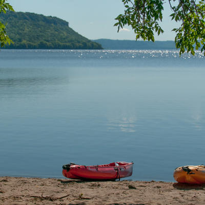 Lake Pepin with kayaks sitting on sandy shore and large hill covered in greenery in background. Photo by Dan Traun.