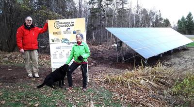 Man, woman and black lab standing next to a solar sign and a photo voltaic solar array.