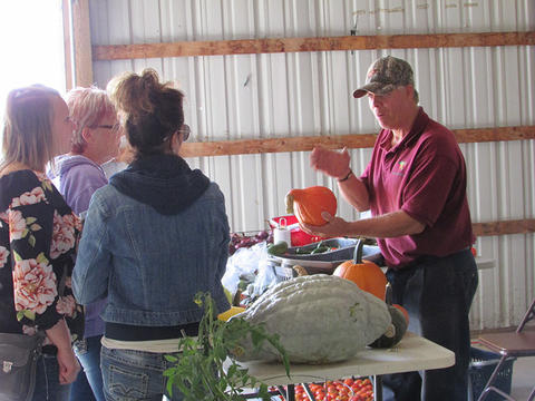 Male farmer holding an orange squash while talking to women about his produce. Table with a variety of squash on it.