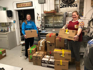 Two women hold grocery boxes smiling in a warehouse. They have packed 14-day meal kits stacked in front of them.
