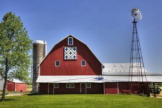 Red dairy barn with silo and windmill on a farm