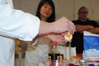 This image features a close up on the chef's hands as she cracks open an egg. Other baking supplies is surrounding the table. Two women in the background are standing and watching the chef.