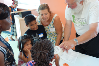 Two adults are reviewing recipes with three children in a Cooking Matters class.