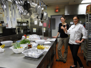 A chef and her assistant stand smiling with thumbs up in a commercial kitchen. Produce is on the counter in preparation for class. Pots, pans and other kitchen utensils hang from the ceiling. The kitchen countertop has fresh produce and recipes in preparation for cooking in the class.